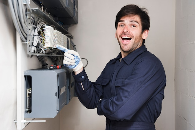 Portrait of happy male electrician pointing at circuit board Premium Photo