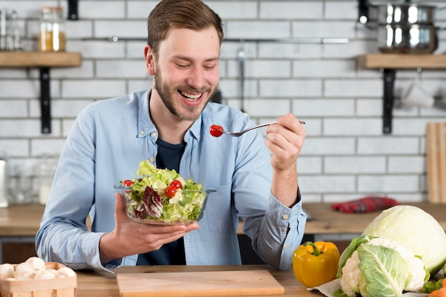 Portrait of a happy man eating fresh salad in the kitchen Free Photo