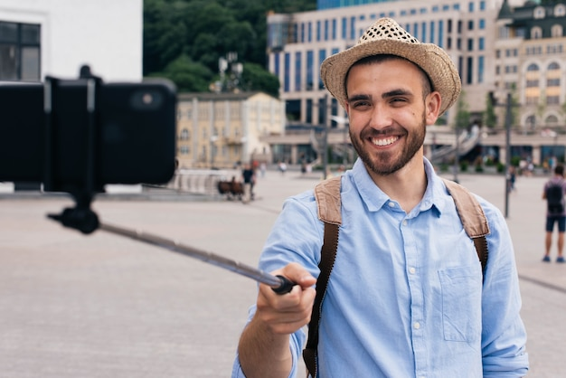 Portrait of happy man wearing hat taking selfie at outdoors Free Photo