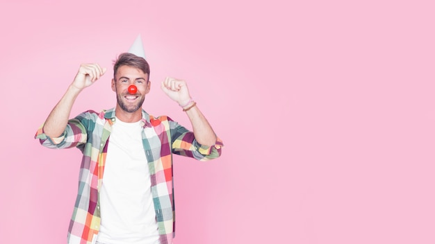 Portrait of a happy man with clown nose on pink background Free Photo