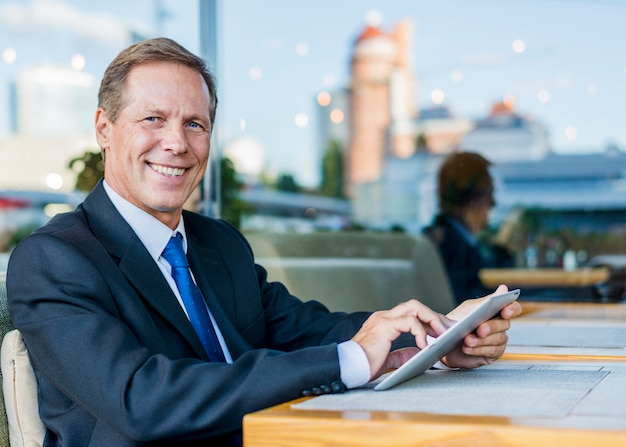 Portrait of a happy mature businessman using digital tablet in restaurant Free Photo