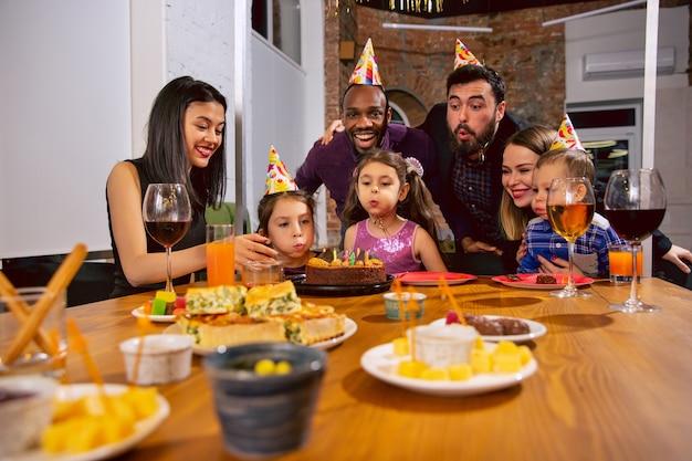 Ritratto di famiglia multietnica felice che celebra un compleanno a casa. grande famiglia che mangia snack e beve vino mentre saluta e si diverte i bambini. celebrazione, famiglia, festa, concetto di casa. Foto Gratuite