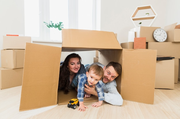 Portrait of a happy parents playing with toddler boy inside the cardboard box Free Photo