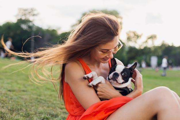 Ritratto di felice bella donna seduta sull'erba nel parco estivo, tenendo il cane boston terrier, sorridente stato d'animo positivo, indossa un abito arancione, stile alla moda, occhiali da sole, giocando con animali domestici Foto Gratuite