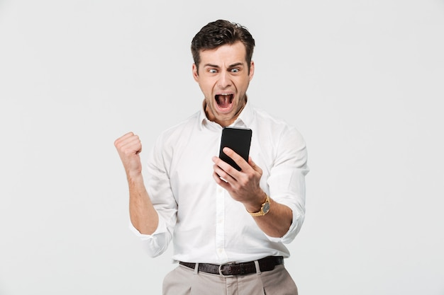 Portrait of a happy satisfied man looking at mobile phone Free Photo