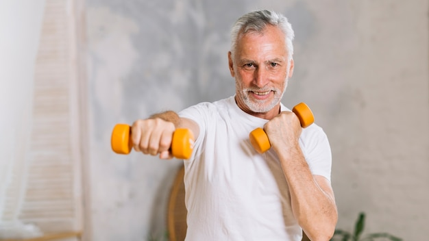 Portrait of happy senior man lifting weights Free Photo