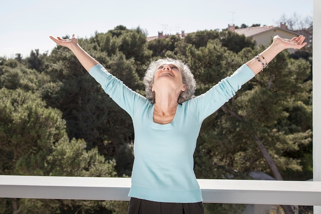 Portrait of happy senior woman standing with raised arms Free Photo