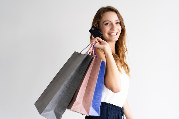 Portrait of happy shopper with shopping bags and credit card. Free Photo