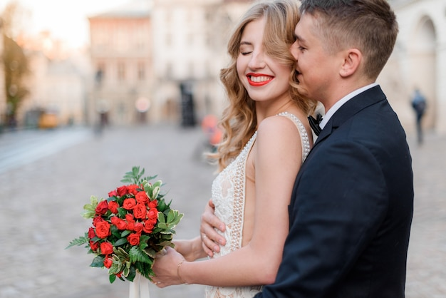 Portrait of happy smiled couple with bouquet made of red roses outdoors with closed eyes, romantic date Free Photo