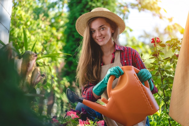 Portrait of happy smiling gardener woman in hat and apron with watering can in home garden. gardening and floriculture Premium Photo