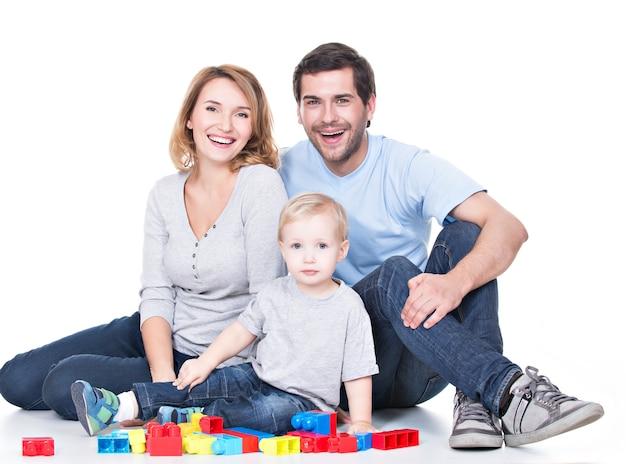 Ritratto di giovani genitori sorridenti felici che giocano con un bambino - isolato su bianco Foto Gratuite