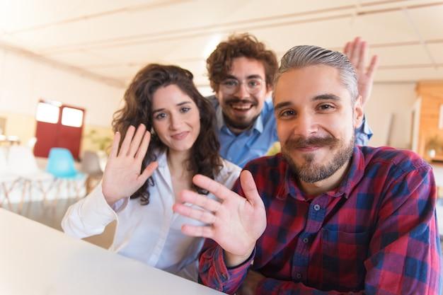 Portrait of happy successful creative team waving hello Free Photo