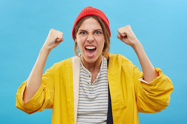 Portrait of happy successful young caucasian woman winner wearing red hat and yellow raincoat rejoicing over victory, success or good positive news with clenched fists, cheering, screaming in joy Free Photo