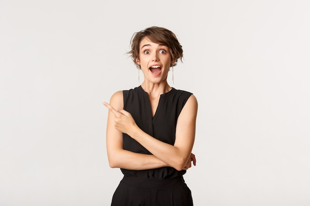 Portrait of happy and surprised caucasian woman open mouth fascinated, pointing upper left corner at promo banner, white. Premium Photo