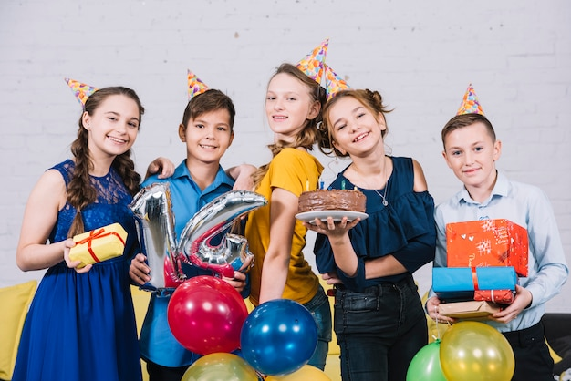 Portrait of happy teenage friends enjoying the birthday by holding birthday cake; gifts and number 14 foil balloon Free Photo