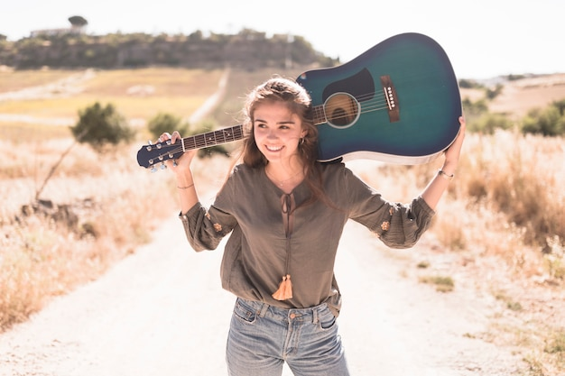 Portrait of a happy teenage girl holding guitar at outdoors Free Photo