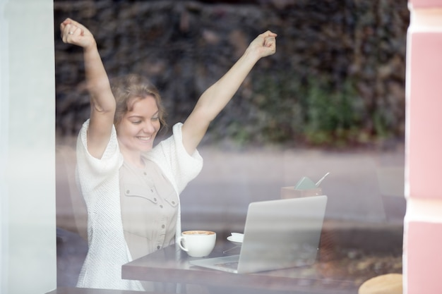 Portrait of happy woman in coffee shop celebrating success with her hands up Free Photo