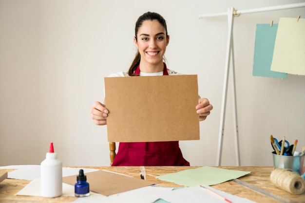 Portrait of a happy woman holding handmade brown paper Free Photo
