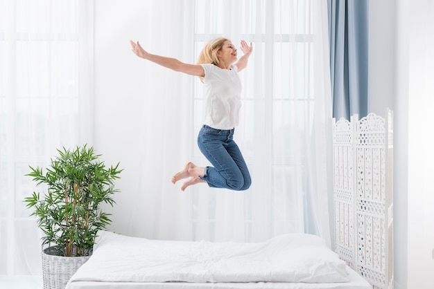 Portrait of happy woman jumping in bed Free Photo