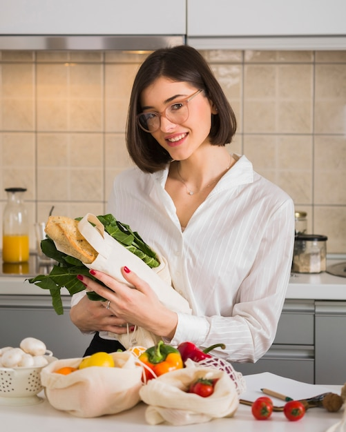 Portrait of happy woman posing with groceries Free Photo
