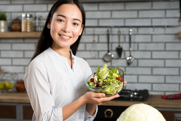 Portrait of happy woman showing fresh mixed vegetable salad in kitchen Free Photo