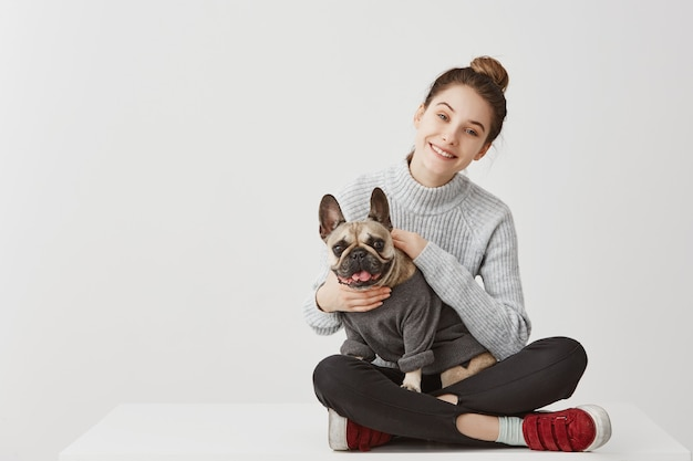 Portrait of happy young adult in good mood sitting on table at home crossed legs. happy housewife fondling french bulldog with pleasure. copy space, family concept Free Photo