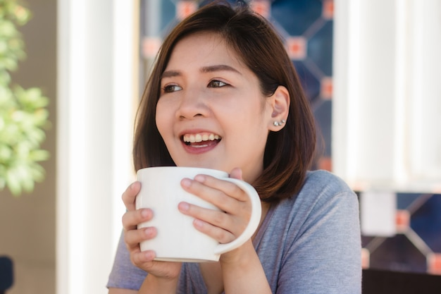 Portrait of happy young asian business woman with mug in hands drinking coffee in the morning Free Photo