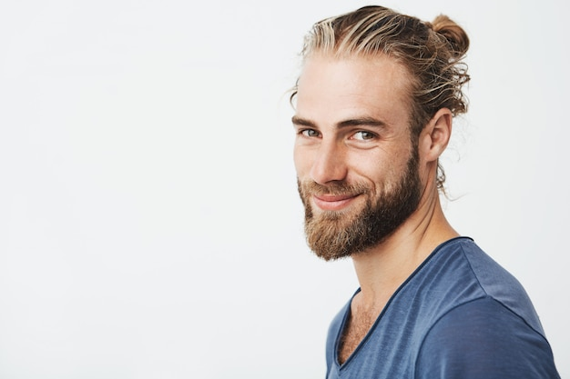 Portrait of happy young bearded guy with fashionable hairstyle and beard Free Photo