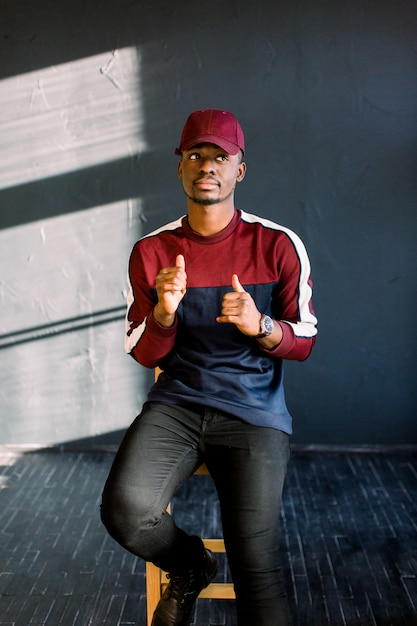 Portrait of happy young black african guy in red baseball cap sitting in a studio on a wooden chair on a dark background . Premium Photo