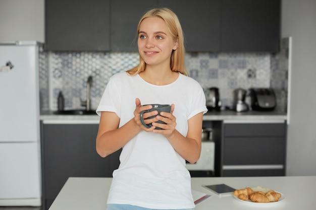 Ritratto di felice giovane donna bionda di buon umore si appoggia sul tavolo, sorridendo Foto Gratuite
