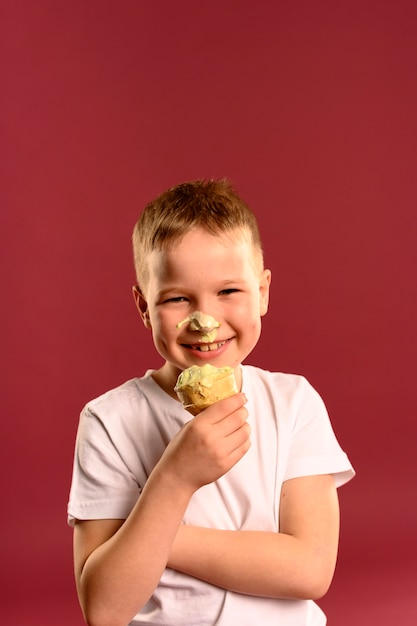 Portrait of happy young boy eating ice cream Free Photo