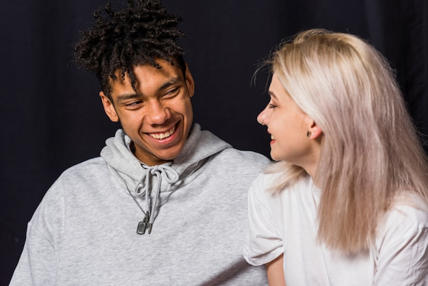 Portrait of happy young couple against black background Free Photo