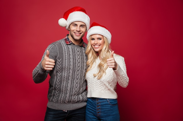 Ritratto di una giovane coppia felice in cappelli di natale Foto Gratuite