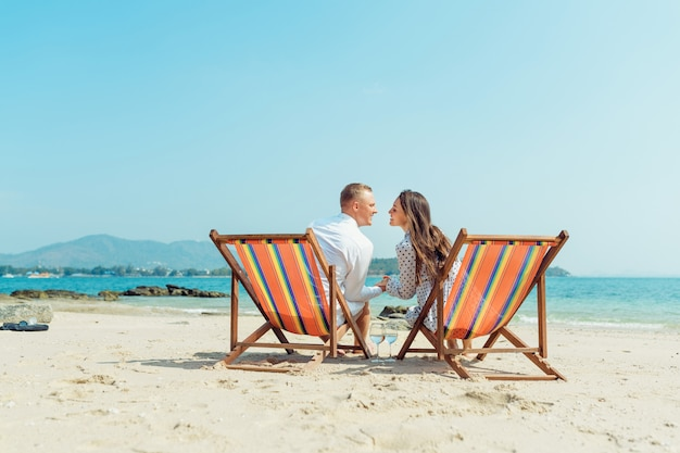 Portrait of happy young couple hugging near with deck chairs in luxury beach hotel Premium Photo