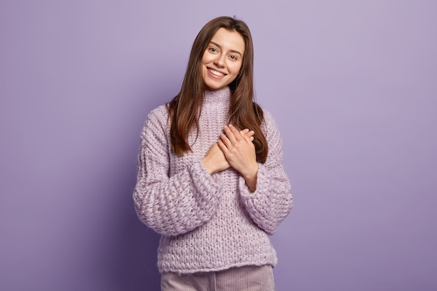 Portrait of happy young european woman keeps hands on breast, shows heart gesture, expresses gratitude, being thankful, models against purple wall body language. monochrome. people and devotion Free Photo
