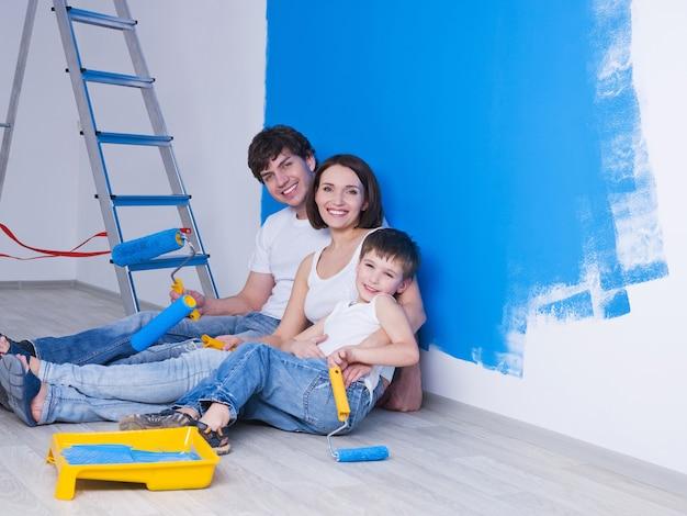 Ritratto di giovane famiglia felice con il piccolo figlio seduto vicino al muro dipinto Foto Gratuite