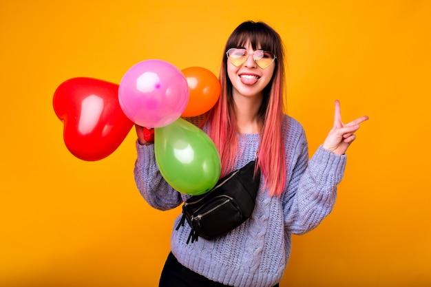 Ritratto di donna felice giovane hipster che mostra gesto ok e ridendo, maglione blu accogliente, occhiali alla moda e borsa, che tiene palloncini colorati, atmosfera di festa. Foto Gratuite