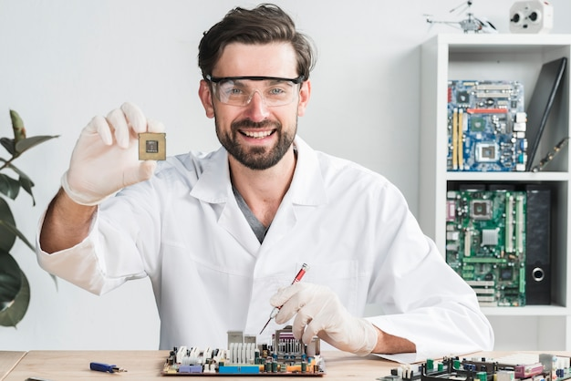Portrait of a happy young male technician holding computer chip Free Photo