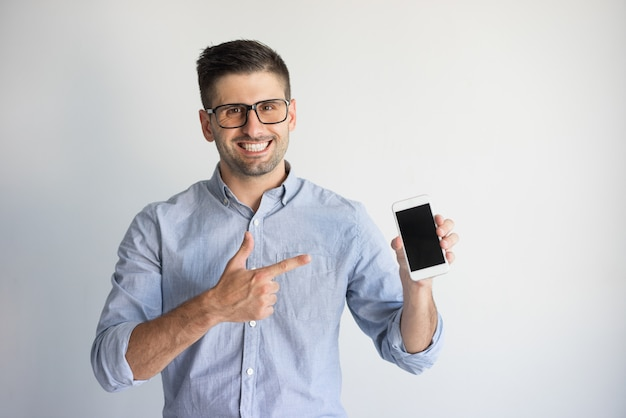 9ab4d36b405 Portrait of happy young man in eyeglasses showing new smartphone ...