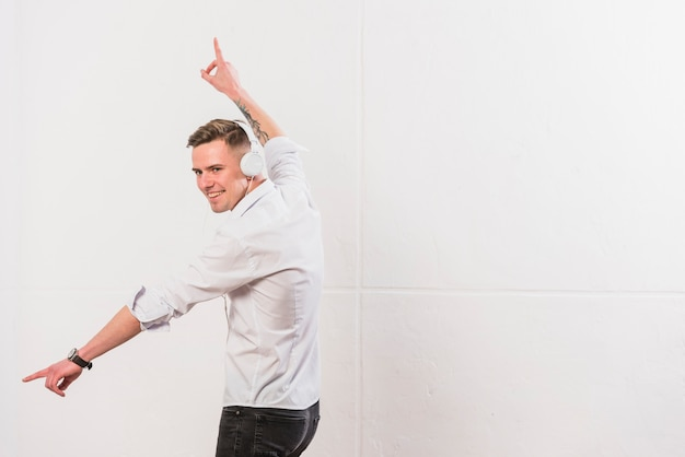 Portrait of a happy young man listening music on headphone dancing against white wall Free Photo