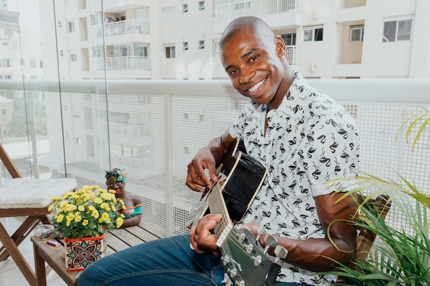Portrait of a happy young man sitting in balcony playing guitar looking at camera Free Photo