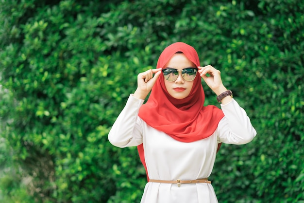 Portrait of happy young muslim woman red hijab over blurred the green field Premium Photo