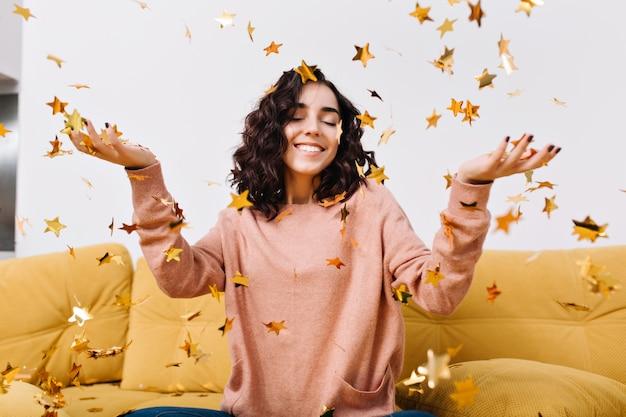 肖像画幸せな若い女、身も凍るように楽しんで、モダンなアパートメントのソファに落ちる黄金のティンセルの中で目を閉じて笑っています。リラックス、幸せ、真のポジティブな感情 無料写真