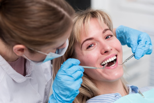 Portrait of happy young woman at the dentist Free Photo