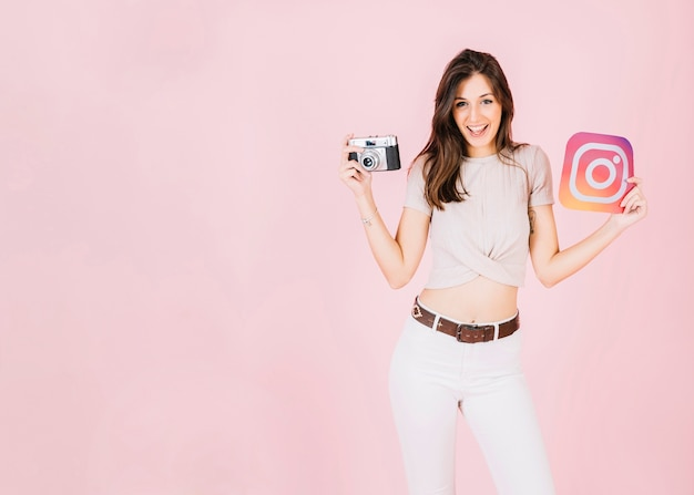 Portrait of a happy young woman holding camera and instagram icon Free Photo