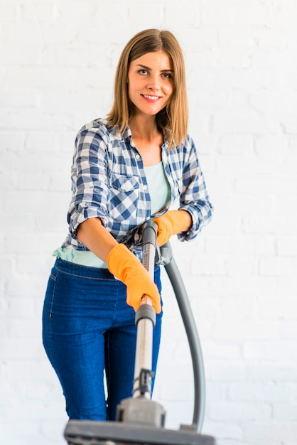 Portrait of a happy young woman holding vacuum cleaner Free Photo