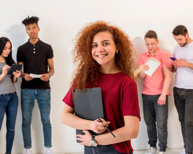 Portrait of happy young woman looking at camera holding clipboard and pencil in front of her friends Free Photo