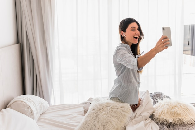 Portrait of a happy young woman sitting on bed taking making video call on mobile phone Free Photo