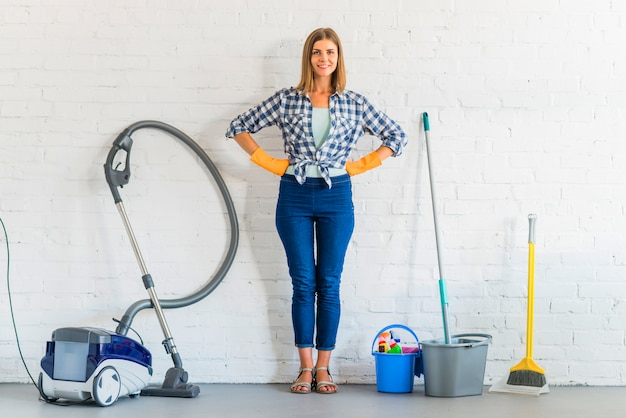 Portrait of a happy young woman standing in front of brick wall with cleaning equipments Free Photo
