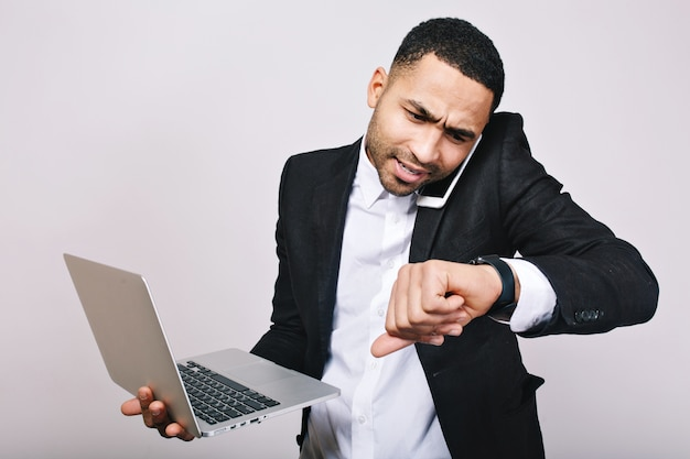 白いシャツ、黒いジャケットが電話で話していると時計を見ての肖像画勤勉忙しい若い男。スタイリッシュなビジネスマン、witjラップトップ、作業、会議の時間。 無料写真